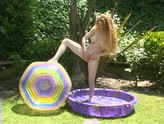 Big tittied red head masturbates in a kiddies pool outside.