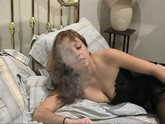 Woman lying in bed smoking